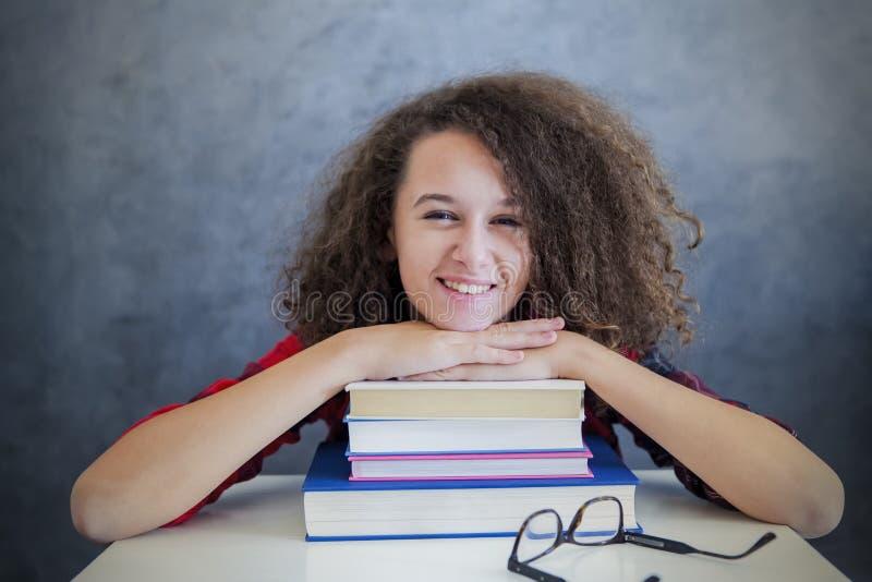 Остатки девушки вьющиеся волосы предназначенные для подростков от учить на книгах стоковые изображения rf