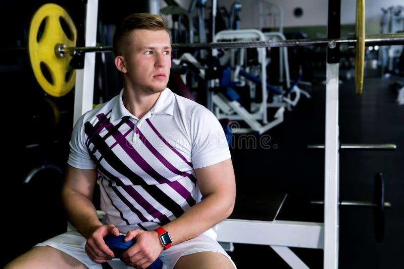 Остатки спортсмена между наборами в тренировке веса стоковое фото rf