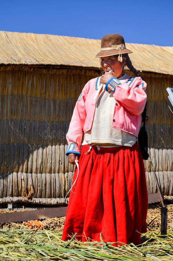 ОСТРОВА UROS ПЛАВАЯ, PUNO, ПЕРУ 31-ОЕ МАЯ 2013: Неопознанная родная женщина нося традиционную одежду ест сахарный тростник стоковое фото rf