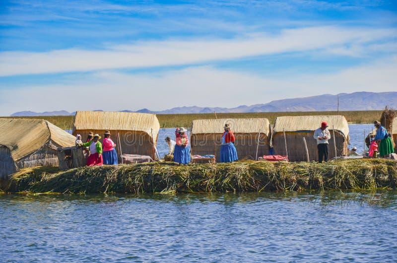 ОСТРОВА UROS ПЛАВАЯ, PUNO, ПЕРУ 31-ОЕ МАЯ 2013: Традиционно одетые люди Aymara Uros живут на этих островах построенных на платфор стоковые фото