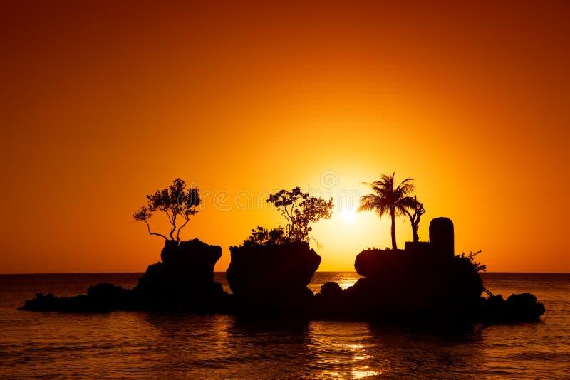 Остров ладоней на море захода солнца стоковые фото