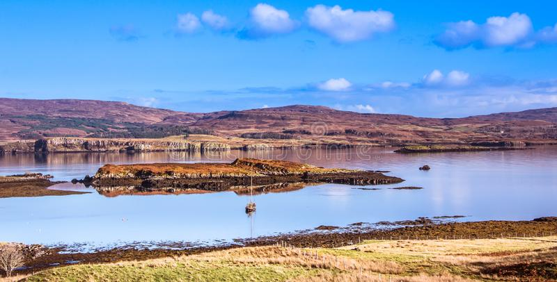 Остров ландшафта Skye - шлюпка яхты на озере Dunvegan с горами, вереске покрыла холмы и голубое небо на заднем плане стоковое изображение rf