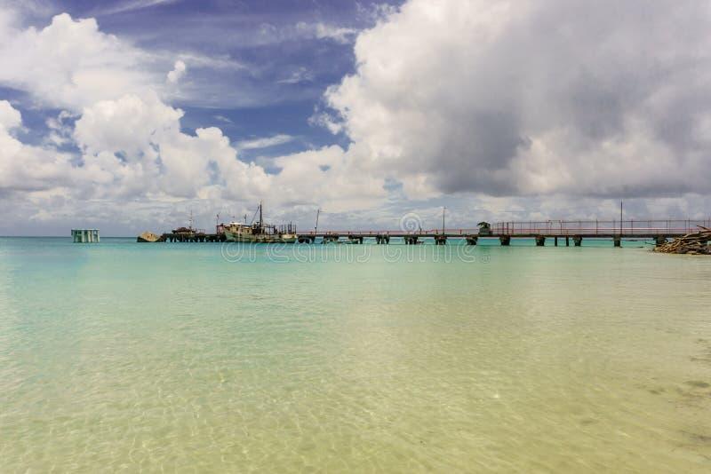 Остров мозоли, Никарагуа - 10-ое мая 2017: Старый карибский док со старым кораблем на тропическом пляже с белым песком стоковые изображения rf