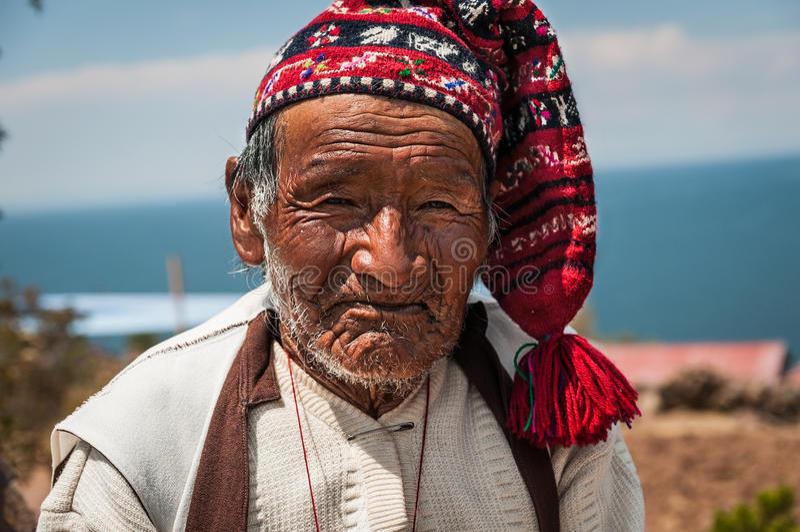 ОСТРОВ TAQUILE, PUNO, ПЕРУ - 13-ОЕ ОКТЯБРЯ 2016: закройте вверх по портрету старого перуанского человека одевая традиционную связ стоковое изображение
