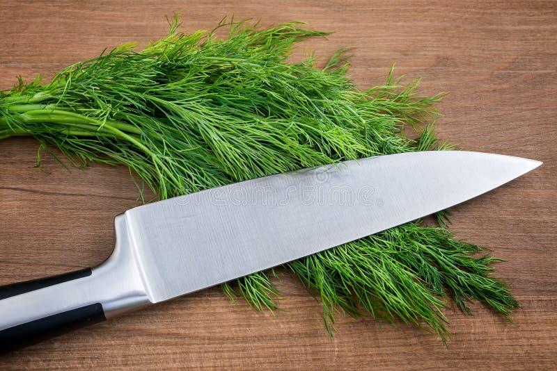 Острый профессиональный нож шеф-повара на пуке свежего зеленого укропа на коричневой деревянной разделочной доске Свежие зеленые  стоковые изображения
