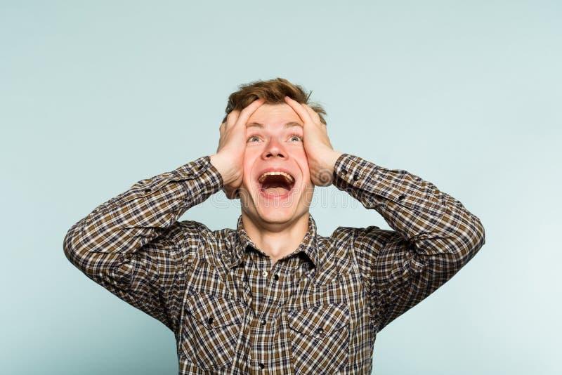 Осчастливленная эмоция счастливого excited человека схватывая головная стоковое фото rf
