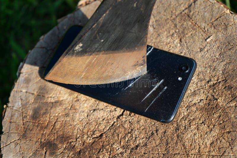 Ось режет телефон Разрушьте нововведение Поступок вандализма Смартфон на пне Смартфон около оси Ось во пне стоковая фотография