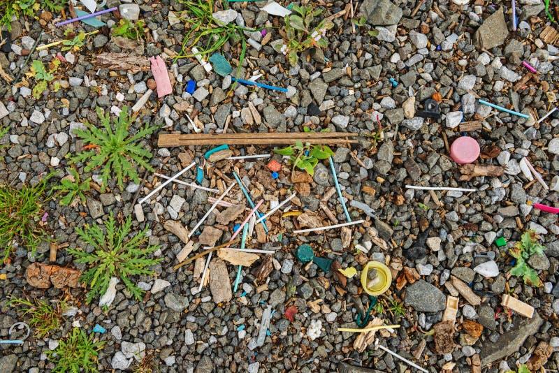 Отброс на пляже около большого города Используемые грязные пластиковые ручки и другой отброс ( стоковое фото rf