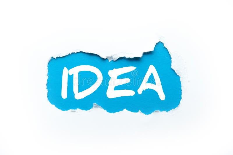 """Отверстие в белой предпосылке, надписи """"идее """"на сини стоковые изображения rf"""