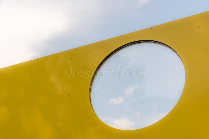 Отверстие в желтой стене и голубом небе на заднем плане стоковые фотографии rf