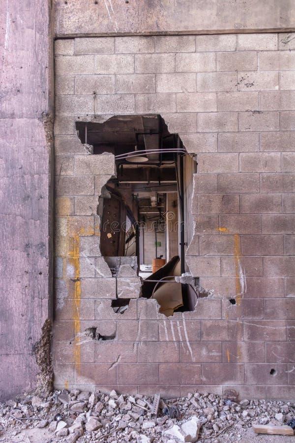 Отверстие в кирпичной стене в получившемся отказ загубленном здании стоковое изображение