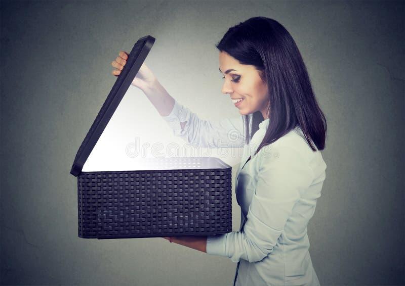 Отверстие женщины смотря в подарочную коробку при яркий свет приходя вне стоковые фотографии rf