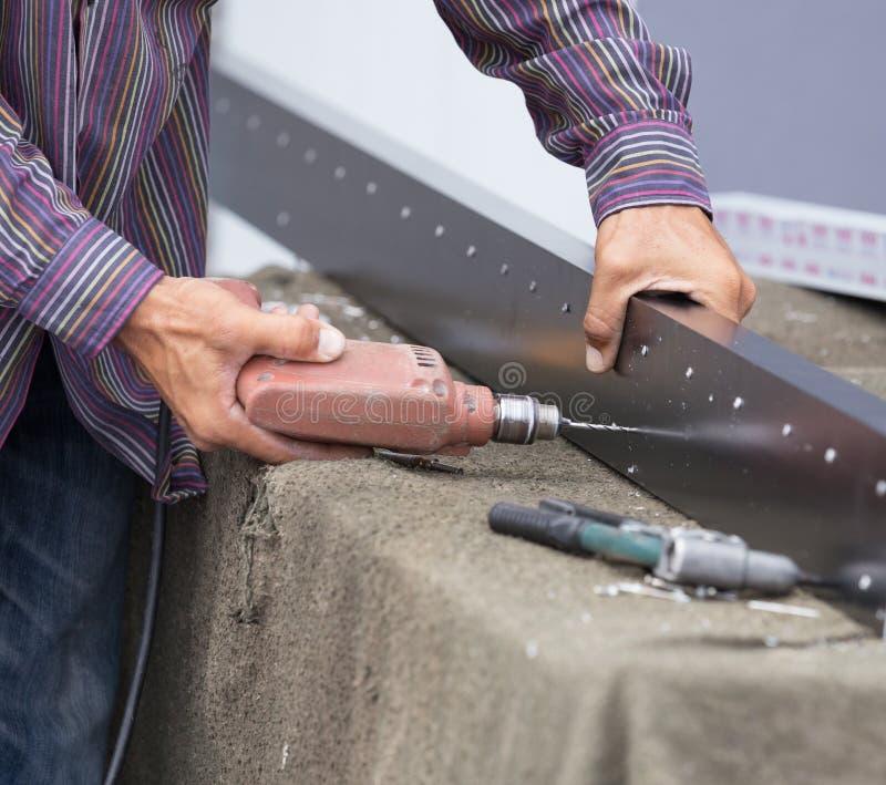 Отверстия работника сверля в алюминиевой рамке конструкции с избирают стоковые фотографии rf