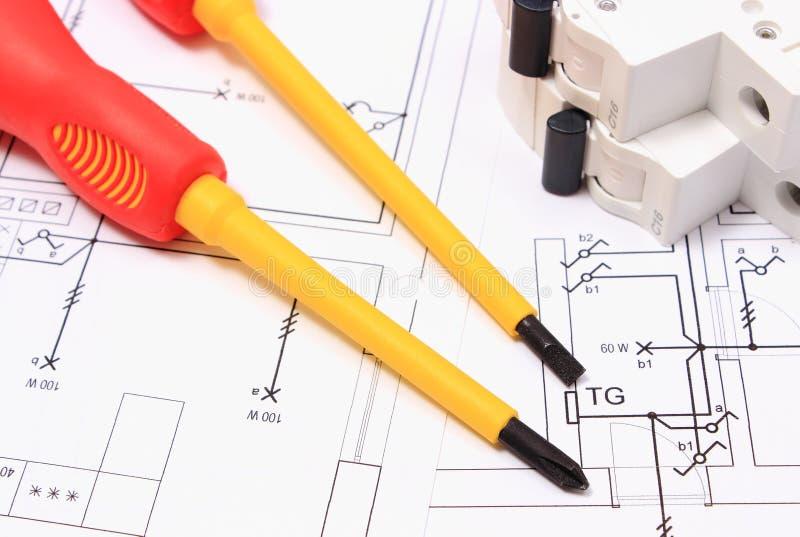 Отвертка и электрический взрыватель на чертеже конструкции дома стоковое изображение