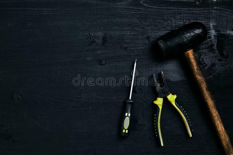Отвертки, молоток, плоскогубцы и инструменты на черном деревянном столе Взгляд сверху стоковые фотографии rf