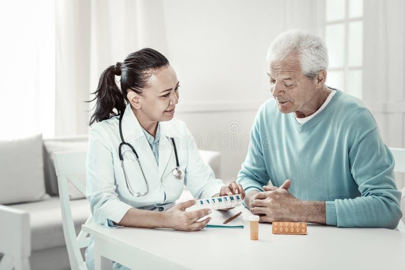 Ответственный серьезный доктор сидя и объясняя инструкция пилюлек стоковое изображение
