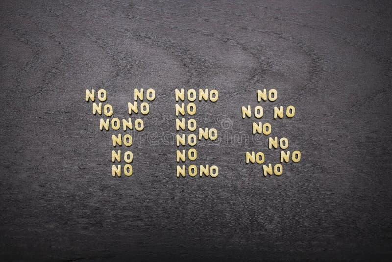 Ответ да составил комплекта слов никаких, с малыми письмами макаронных изделий на темной предпосылке деревянной доски, показывая  стоковое изображение rf