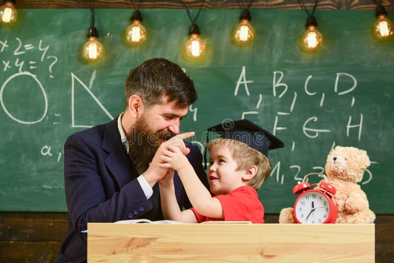 Отвлекать ребенк жизнерадостный пока изучающ, синдром дефицита внимания Будьте отцом с бородой, учителем учит сыну, мальчику учит стоковая фотография rf