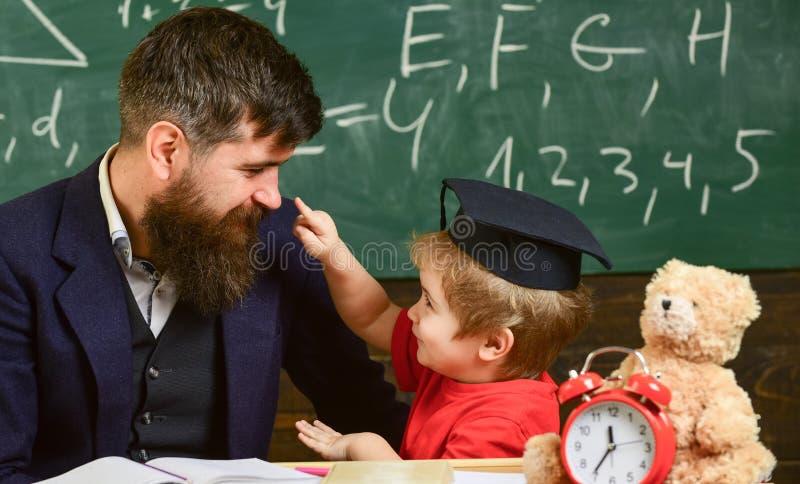 Отвлекать ребенк жизнерадостный пока изучающ, синдром дефицита внимания Капризная концепция ребенка Учитель и зрачок в mortarboar стоковая фотография