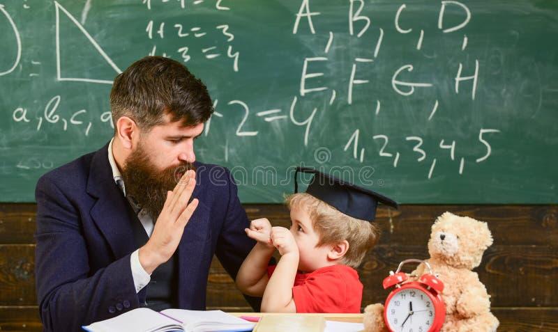 Отвлекать ребенк жизнерадостный пока изучающ, синдром дефицита внимания Шаловливая концепция ребенка Учитель и зрачок в mortarboa стоковые фотографии rf