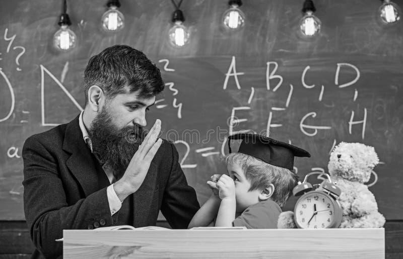 Отвлекать ребенк жизнерадостный пока изучающ, синдром дефицита внимания Учитель и зрачок в mortarboard, доске на предпосылке стоковое фото