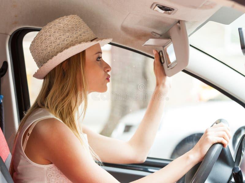 Отвлеченная женщина управляя ее автомобилем смотря в зеркале стоковое изображение
