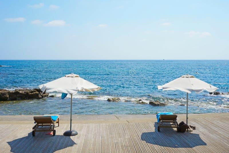 Отдохните на тропических зонтиках побережья и 2 пустых кресла для отдыха стоят на деревянной палубе стоковая фотография