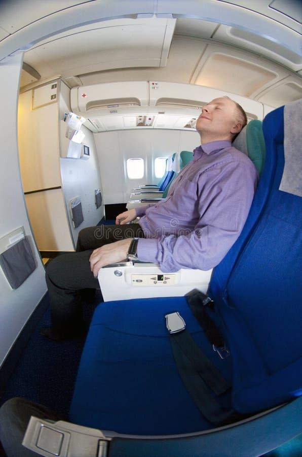 отдыхать бизнесмена самолета стоковое изображение rf