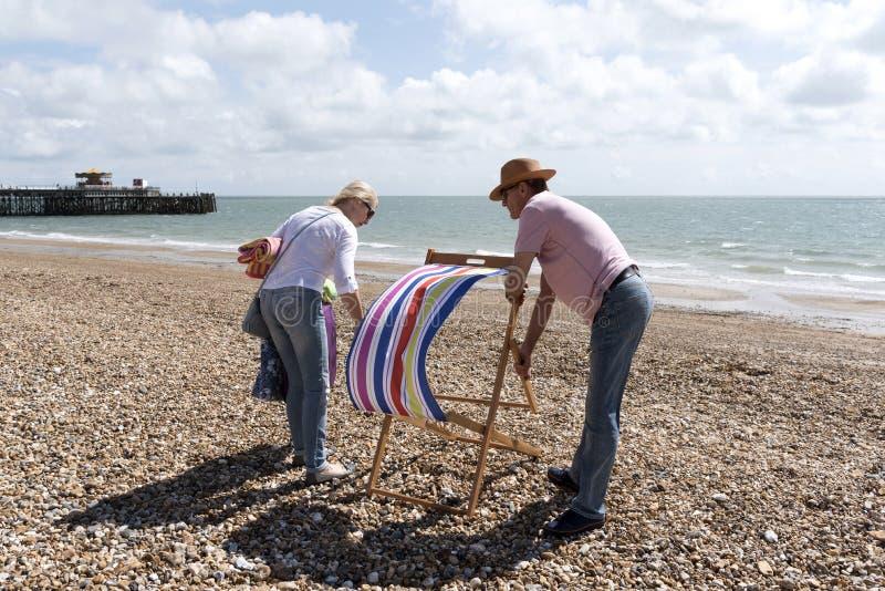 Отдыхающие раскрывая deckchair на пляже стоковое фото