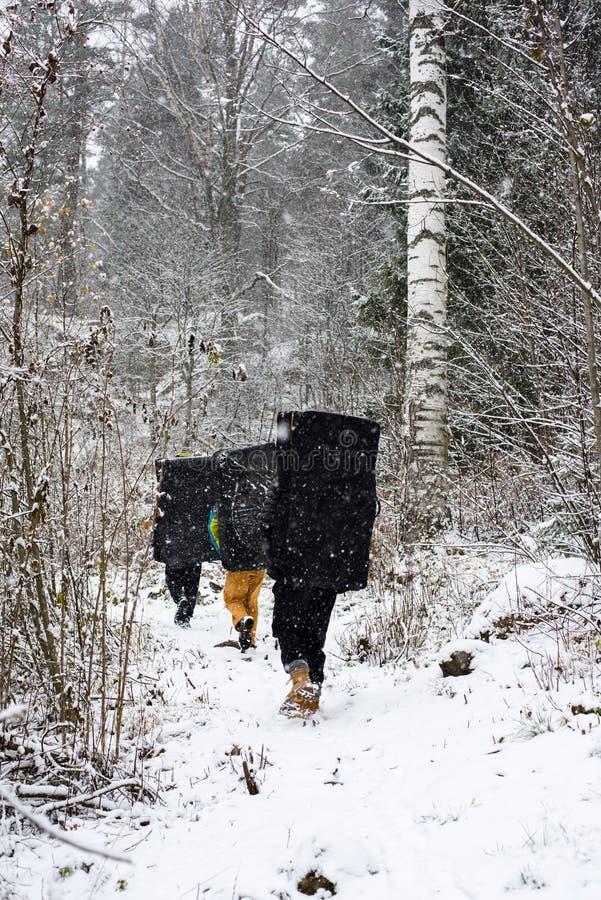 Отдых зимы внешний Альпинисты утеса с пусковыми площадками аварии в снежном лесе, стоковое фото