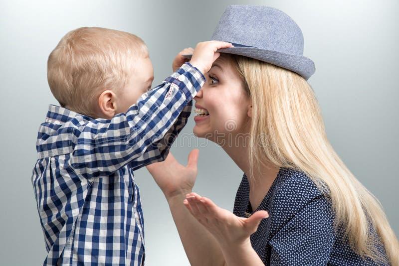 Отдых семьи Мальчик дает для того чтобы положить дальше модную шляпу к его матери стоковые изображения