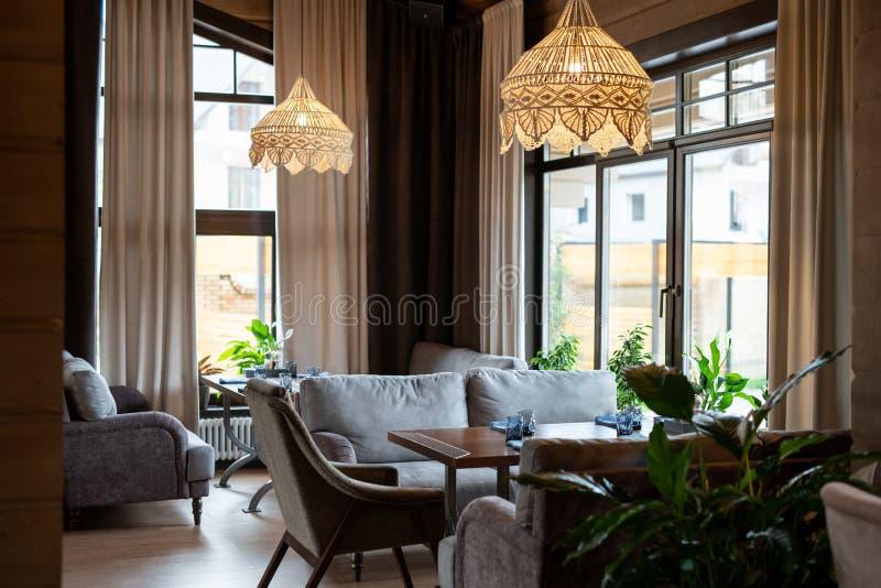 Отель расположен в центре роскошного ресторана с деревянными столами и удобными диванами стоковые фотографии rf