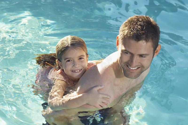 Отец давая автожелезнодорожные перевозки дочери в бассейне стоковые фотографии rf