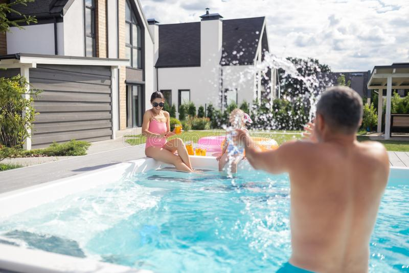 Отец брызгая воду на его дочери и жене в бассейне стоковые изображения
