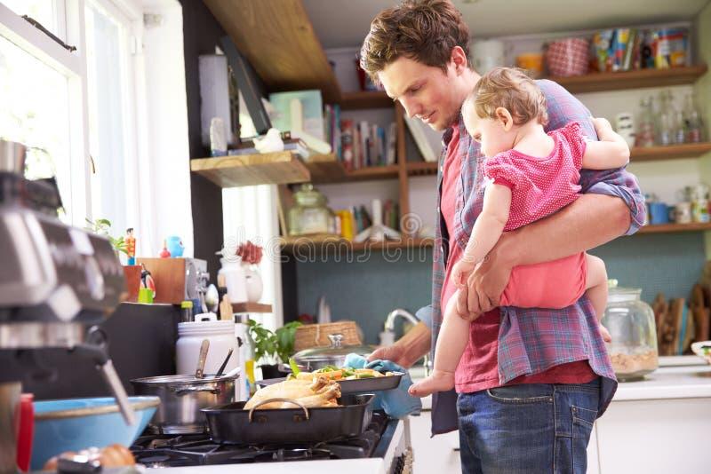 Отец варя еду пока держащ дочь в кухне стоковая фотография