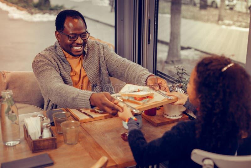 Отец давая деревянную плиту с сэндвичем его милой дочери стоковая фотография rf
