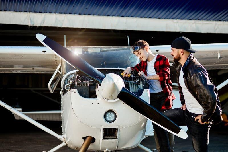 Отец давая инструкции сыну как сделать для того чтобы проверить вверх для небольших самолетов стоковые фото