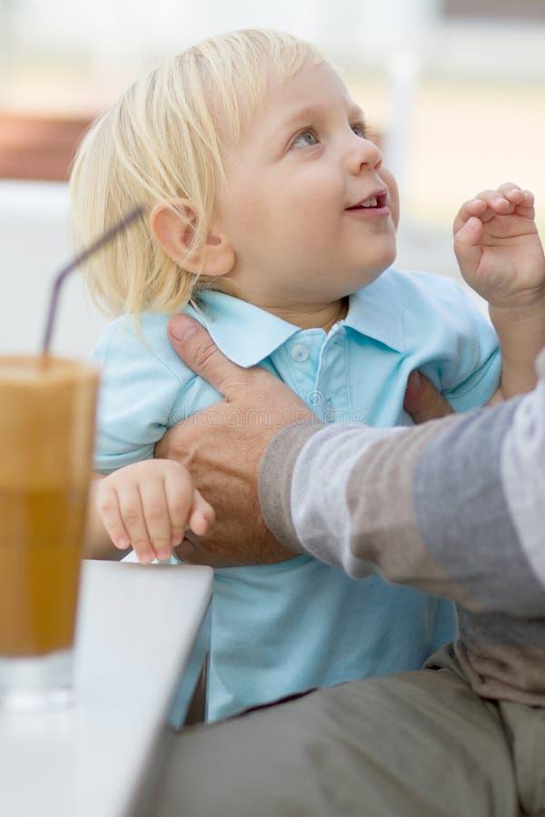 Отец держа его маленького сынка стоковые изображения