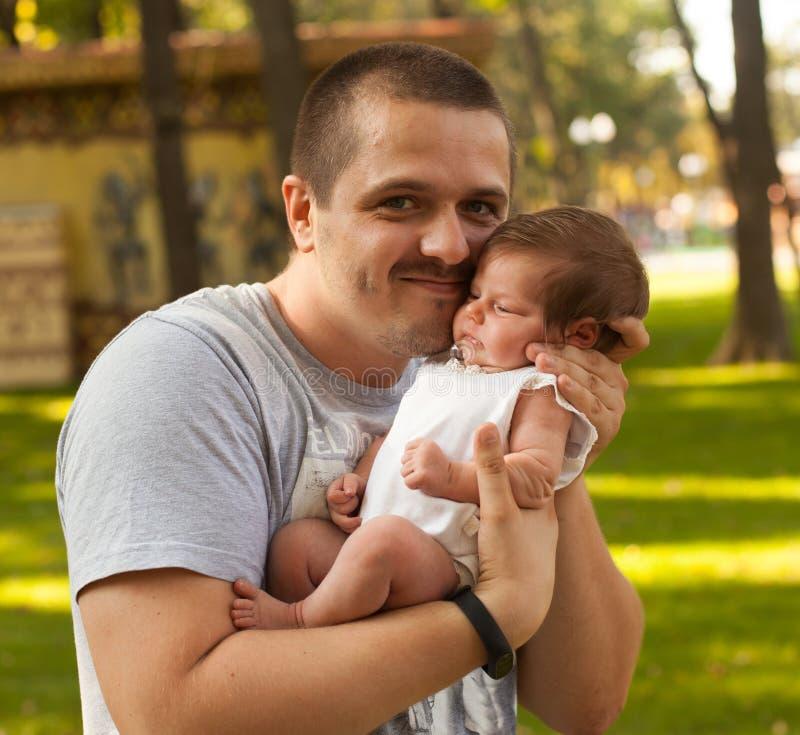Отец держа меньший милый newborn ребенка стоковые изображения rf