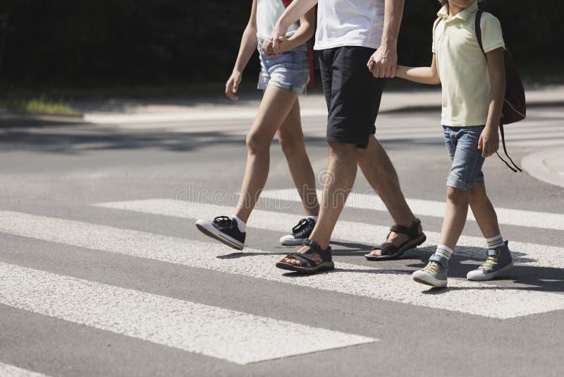 Отец держа руки с его детьми пока на пешеходном переходе стоковая фотография