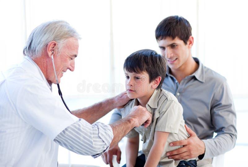 отец доктора мальчика рассматривая его старший стоковая фотография rf
