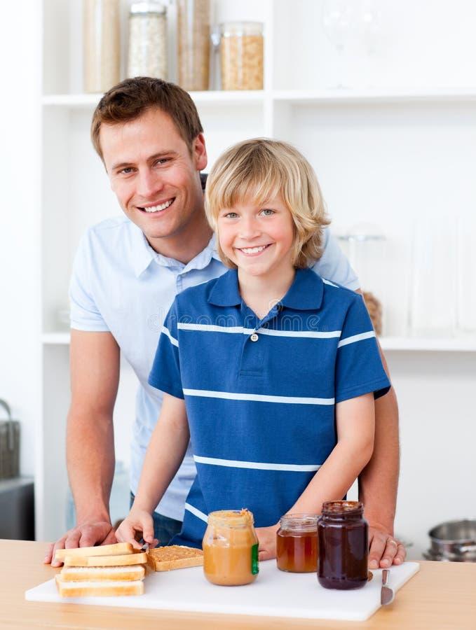 отец завтрака помогая его подготовляет сынка стоковая фотография rf
