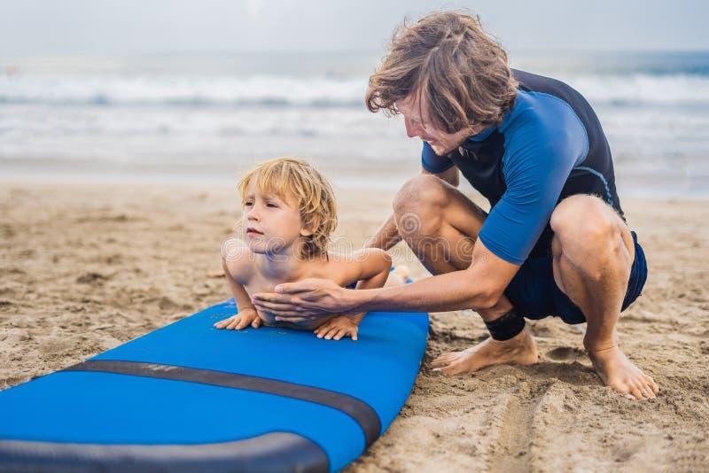 Отец или инструктор уча его 4 - летнему сыну как заниматься серфингом внутри стоковое фото rf