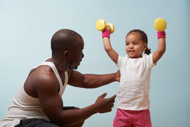Отец инструктируя его меньшую дочь о том, как работать с гантелями дома стоковая фотография rf
