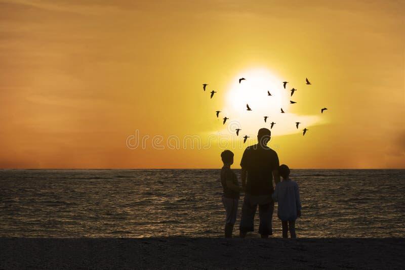 Отец и дети наслаждаясь красивым заходом солнца стоковая фотография rf