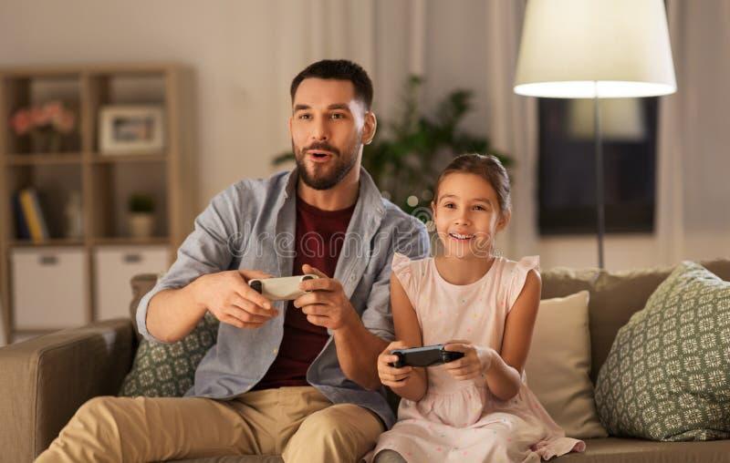 Отец и дочь играя видеоигру дома стоковые изображения rf