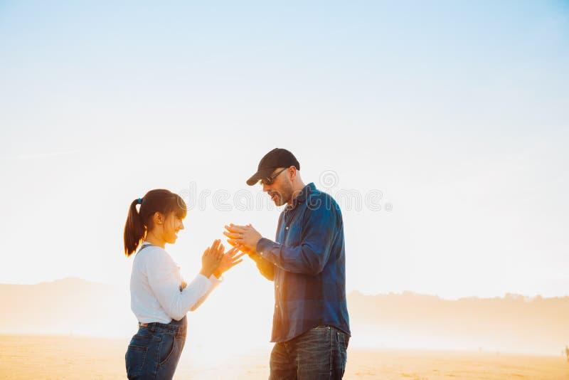 Отец и дочь играя игру рук на пляже на заходе солнца стоковое фото rf