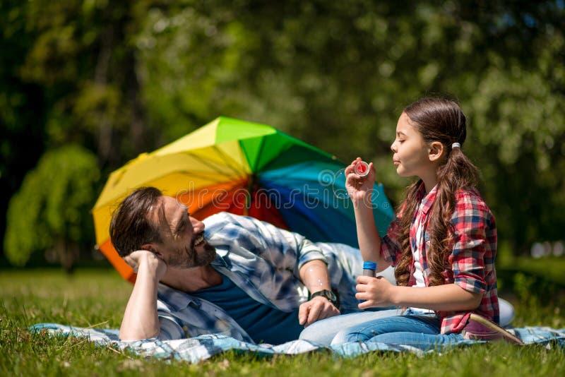 Отец и дочь на голубом одеяле с пузырями мыла в парке Красочный зонтик на предпосылке стоковые фотографии rf