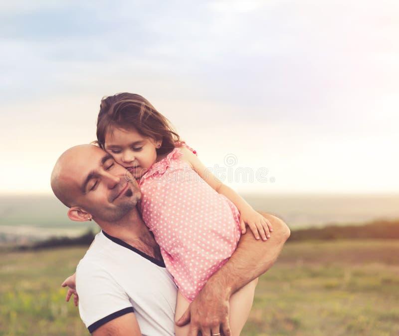 Отец и дочь обнимая на заходе солнца лета стоковое фото rf