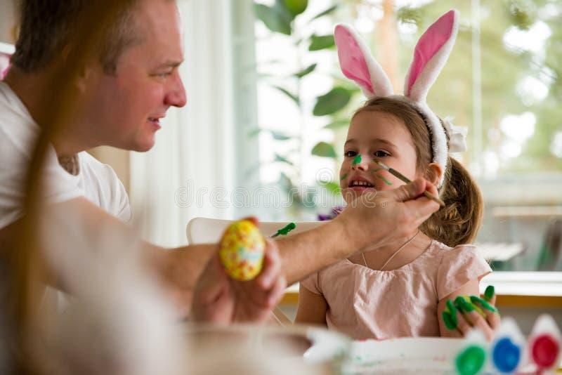 Отец и дочь празднуя пасху, крася яйца с щеткой стоковая фотография rf